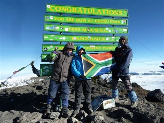 A stunning pic taken of Anthony and Judi with Milton helping hold the South African flag at the summit. ~ Photo by Judi Kurgan