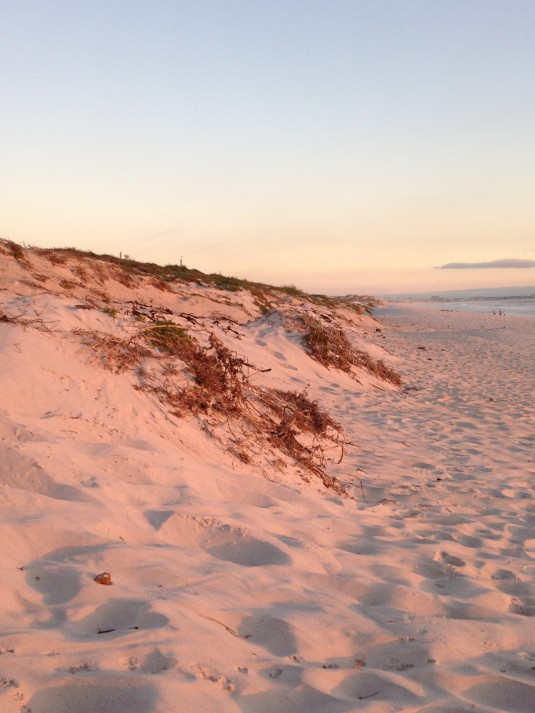 The fading sun splashes the sand around me in soft tones of pink, engulfing everything around in colour.