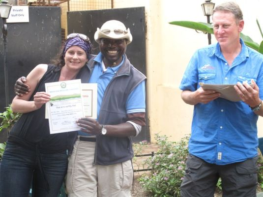 Receiving my two certificates from our lead guide, Dixon. The certificates state I've successfully summited Kilimanjaro. Photo by Simon Bates