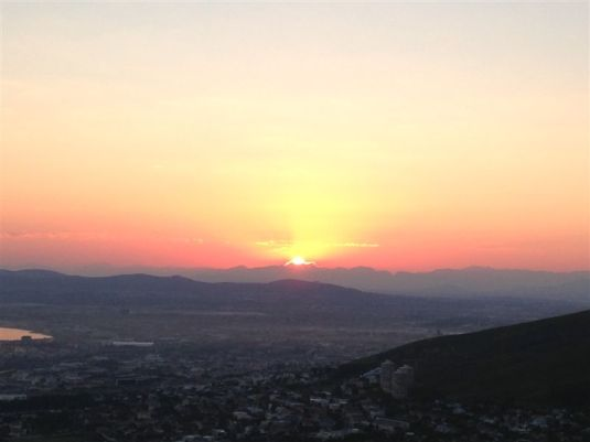 The sun rising over Cape Town below.