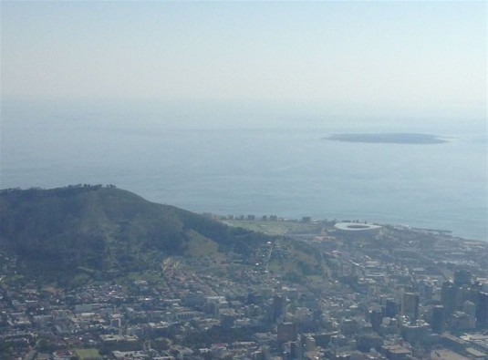 A bit of a hazy view of Signal Hill, The Cape Town Stadium which was built for the Soccer World Cup and Robben Island in the ocean.