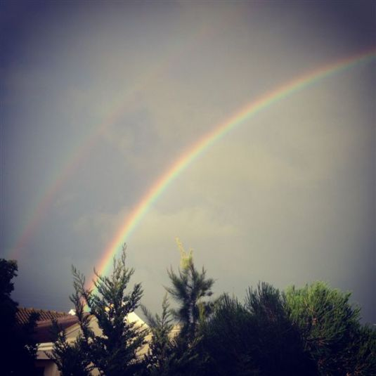 A beautiful double rainbow as seen from my back yard that reached all the way across the sky.
