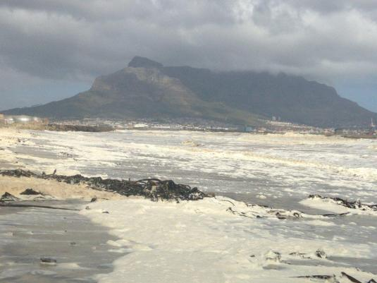 The foam on the shoreline with Table Mountain in the background.
