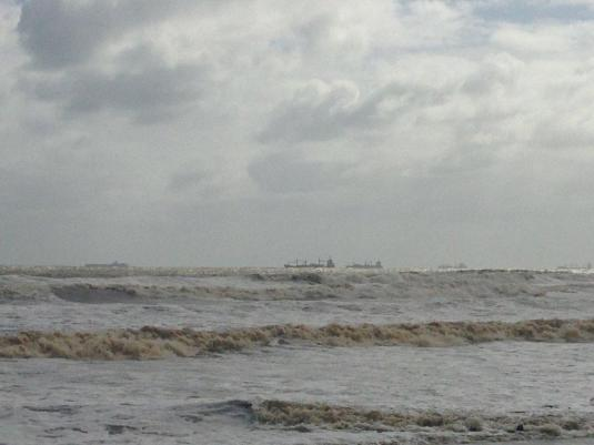 Ships anchored, lining the horizon, unable to enter the harbour until the storm has passed.