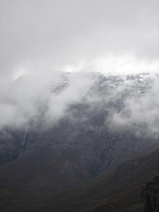 The beauty behind the clouds and the magnificent waterfalls cascading down the mountain slopes across the valley.
