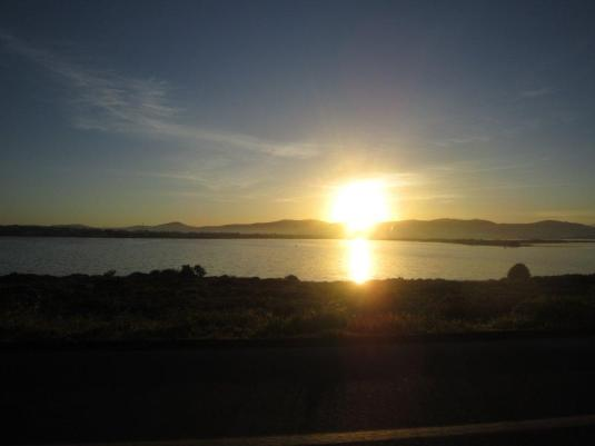 Natalie driving us out out to Kalk Bay, I managed to catch the sun was just popping over the hills across the vlei.