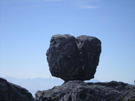 A heart shaped rock balanced on the edge of another rock with the snow-capped mountain peaks in the background.