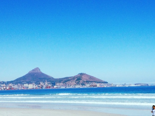 Lions Head and Signal Hill overlooking the Cape Town Stadium with the sea lapping at their feet.