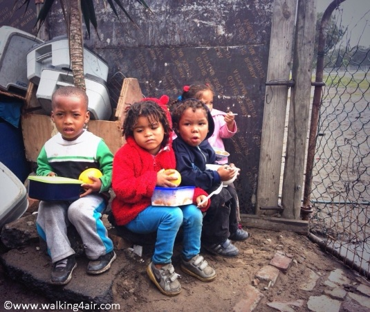 The kiddies sitting outside on cold, wet stones eating their warm meal.