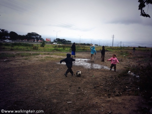 No grass, swings, or slide or pretty flowers, just sand, weeds, puddles and mud make up the children's playground.