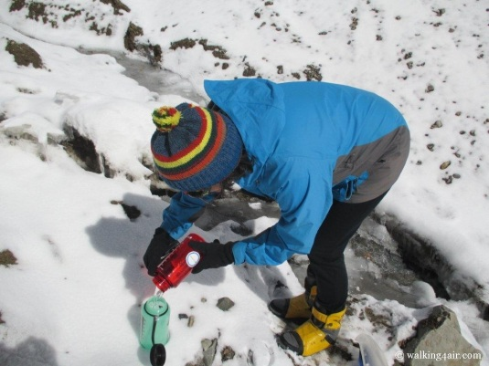 Judi braving the frozen stream to fill up our water bottles.