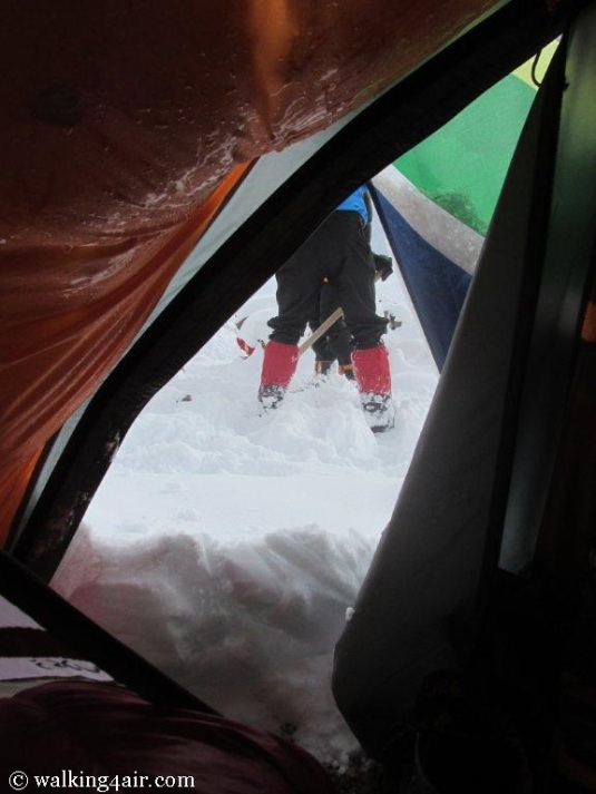 Snowed in at Camp 2! Other teams can be seen scrapping snow away from their tents.